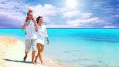 Visa glada unga familj att ha kul på stranden — Stockfoto