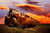 żółty ciągnik na niebo złote surise — Zdjęcie stockowe