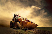 Yellow tractor on golden sunrise sky — Stockfoto