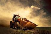 Tractor amarillo en el cielo del amanecer dorado — Foto de Stock