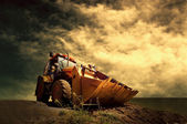 Yellow tractor on golden sunrise sky — Stock Photo