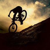 Bir adam muontain-bisiklet, gün batımı silüeti — Stok fotoğraf
