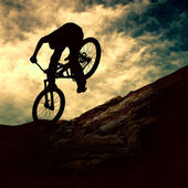 Silhouette of a man on muontain-bike, sunset — Stock Photo