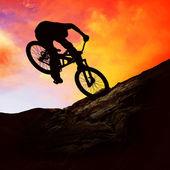Silueta de un hombre en bicicleta de muontain, al atardecer — Foto de Stock