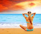 Young beautiful women on the sunny tropical beach in bikini — Zdjęcie stockowe