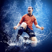 Water drops around football player under water on blue background — Stock Photo