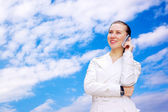 Happy business-woman call by phone on sky background — Stock Photo