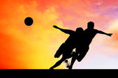 Silhouettes of footballers on the sunset sky — Stock Photo