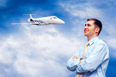 Happy businessman on blue sky with airplane — Stockfoto