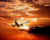Airplane on sunset sky — Stock Photo