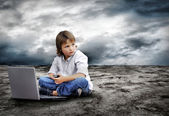 Young boy seating with notebook on the land — Stock Photo