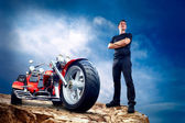 Men with motorbike on the top of mountains. — Stock Photo