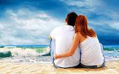 Widok na morze z para siedzi na plaży. — Zdjęcie stockowe