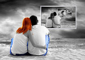 Sea view of a couple sitting on beach and see TV monitor — Stock Photo