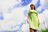 Happy woman on blue sky and green grass background — Stock Photo