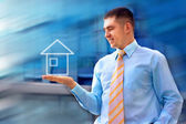 Happy businessman with house in his hand — Stock Photo