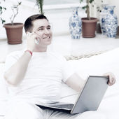 Smiling young man working on laptop computer and call by phone a — Photo
