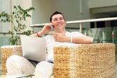 微笑着的年轻男人在便携式计算机上的工作和通过电话叫 — 图库照片