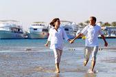 Visa lyckliga unga paret promenerar på stranden, hand i hand. — Stockfoto