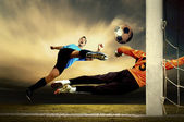 Shoot of football player and goalkeeper — Stock Photo
