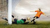 Fotos de jogador de futebol e salto do goleiro no campo de — Foto Stock