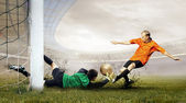 Shoot of football player and jump of goalkeeper on the field of — Стоковое фото