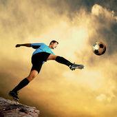Footballer on the top of mountain — Stock Photo