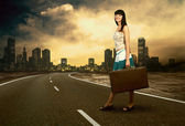 Young woman waiting on the road with her vintage baggage — Stock Photo