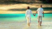 Vista traseira de um casal caminhando na praia, de mãos dadas. — Foto Stock