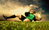 Jump of football goalman on the outdoor field — Stock Photo