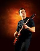 Rock guitarist play on the electric guitar, orange sky backgroun — Stock Photo