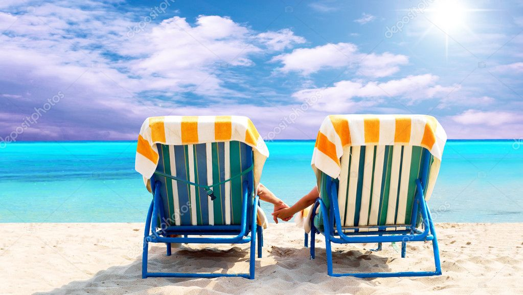 Rear view of a couple on a deck chair relaxing on the beach  Stock Photo #6352710