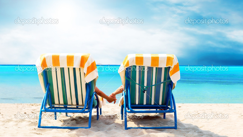 Rear view of a couple on a deck chair relaxing on the beach — Stock Photo #6352713