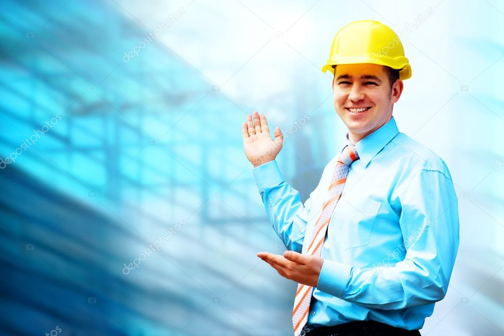 Young architect wearing a protective helmet standing on the building background — Stock Photo #6354451