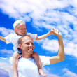 Royalty-Free Stock Photo: Joyful father giving piggyback ride to his son against a sky bac