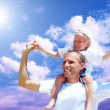 Joyful father giving piggyback ride to his son against a sky bac — Foto Stock