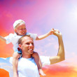 Joyful father giving piggyback ride to his son against a sky bac — Stockfoto