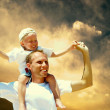 Joyful father giving piggyback ride to his son against a sky bac — Stock Photo