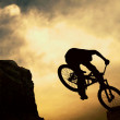 Stock Photo: Silhouette of a man on muontain-bike, sunset