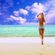 Young beautiful women on the sunny tropical beach in bikini — Stock Photo