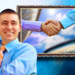 Businessman on the background of picture with two  shaking hands — Stock fotografie
