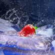 Water drops around strawberry and ice on blue background — Stock Photo