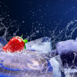 Water drops around strawberry and ice on blue background — Stock Photo #6360269