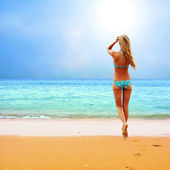 Güneşli tropik sahilde bikinili genç güzel kadın — Stok fotoğraf
