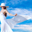 Royalty-Free Stock Photo: Young beautiful women in the white with pareo on the blue sky ba