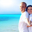 View of happy young couple walking on the beach, holding hands. — Stock Photo #6370572