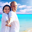 View of happy young couple walking on the beach, holding hands. — Stock Photo #6370574