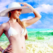 Young beautiful women on the sunny tropical beach in bikini and — Stock Photo