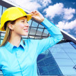 Young architect-woman wearing a protective helmet standing on th — ストック写真