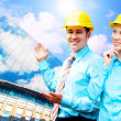 Young architects wearing a protective helmet standing on the bui — Stock Photo #6370657